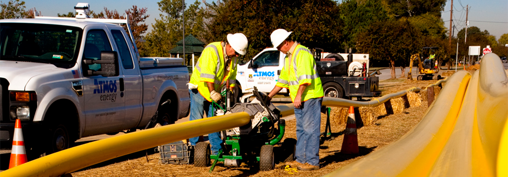 Two employees in yellow vests with wrenches working on a pipeline