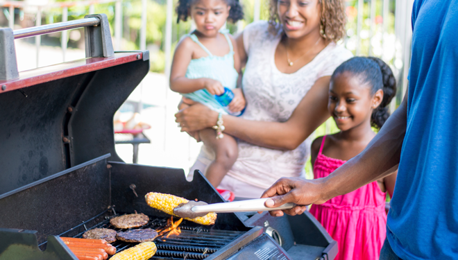 Family grilling outside in the summer on their natural gas grill.