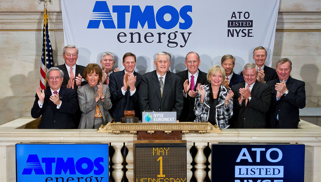 Atmos Energy senior leadership and board of directors standing on the New York Stock Exchange platform with Atmos Energy stock price posted.