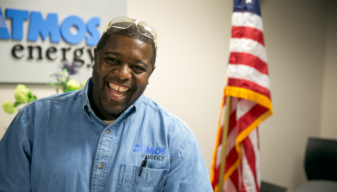Atmos Energy employee standing in front of an American flag